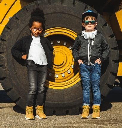 Two Kids wearing CAT shoes and standing next to truck wheel